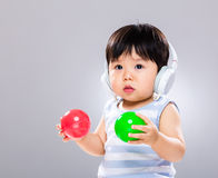 Baby listen to music and play ball. With gray background royalty free stock photography
