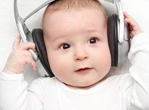 Baby listening music on back Stock Photo
