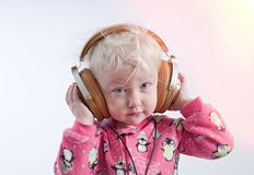 Baby listening music in headphones royalty free stock photography