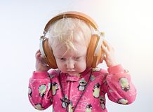Baby listening music in headphones stock photo