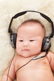 Baby listening to music royalty free stock photos