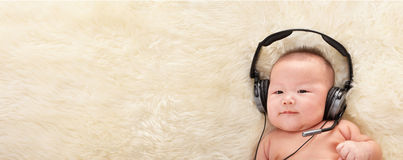 Baby listening to music Stock Photos