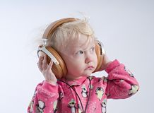 Baby listening music in headphones royalty free stock photo