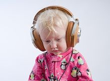 Baby listening music in headphones stock photography