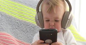 Baby listens headphones holding smartphone stock video footage