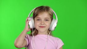Baby listens to music through the headphones. Green screen. Slow motion stock video footage