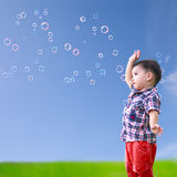 Baby little asian boy standing against blue sky with soap bubble Royalty Free Stock Images