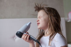 Baby little Girl dries hair, sisters taking care of yourself, th royalty free stock photo
