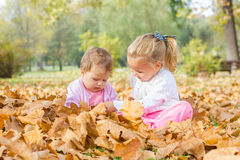 Baby and little girl have fun with autumn leaves Royalty Free Stock Images