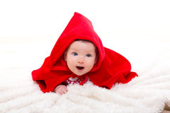 Baby Little Red Riding Hood on white fur. With funny expression Stock Photos