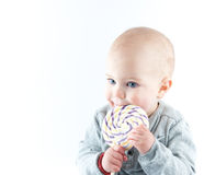 Baby with lollipop. Cute baby boy licking a lollipop Royalty Free Stock Image