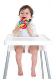 Baby with lollypop. Baby in highchair eating lollypop isolated on white Royalty Free Stock Photos