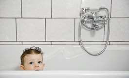 Baby look out from bathtub Stock Photos
