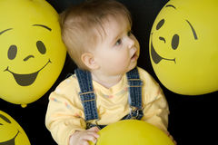 Baby looking at balloons. Baby girl looking at face on balloons, amazed Royalty Free Stock Photography