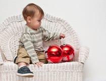 Baby looking at big Christmas ornaments Stock Photo