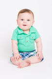 Baby Looking at Camera. 8 month year old baby sits on a white background smiling towards the camera. dressed in a cute green polo shirt and blue plaid shorts Stock Photography