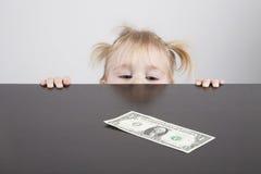 Baby looking at dollar banknote horizontal Royalty Free Stock Photos