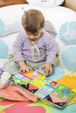 Baby looking down at colorful book with pictures Stock Photography