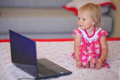 Baby looking into the laptop. Royalty Free Stock Photography