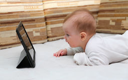 Baby looking at a new tablet PC.  Stock Image