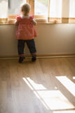 Baby looking out window. Adorable toddler on Tippy Toes looking out window Stock Images