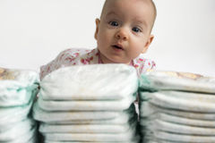 Baby looking over a stack of diapers. Adorable baby girl looking over a stack of diapers Stock Photos