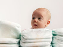 Baby looking over stack of diapers 2. Adorable baby girl looking over a stack of diapers Royalty Free Stock Photo