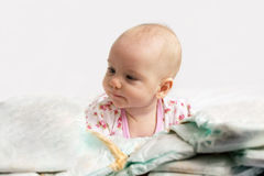 Baby looking at  pile of diapers Royalty Free Stock Images