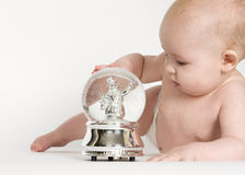 Baby Looking at Snow Globe Stock Images