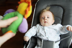 Baby looking at toy Stock Images
