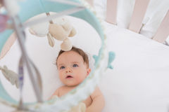 Baby looking at toys hanging in crib Stock Photos
