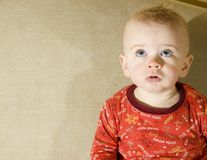 Baby looking up. Baby boy looks up while sitting on couch royalty free stock images