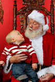 Baby looking up at Santa Royalty Free Stock Photo