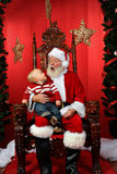 Baby looking up at Santa Claus Royalty Free Stock Photos