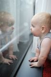Baby looking at the window Royalty Free Stock Photos