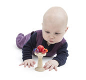Baby looking at wooden toy Stock Photos