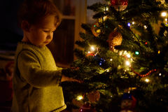 Baby looks at decoration on a Christmas tree Stock Photo