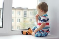 Baby looks out of window Royalty Free Stock Photos