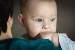a baby looks out the window while sitting in the arms of his mother stock images