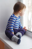 Baby looks out of window Royalty Free Stock Image