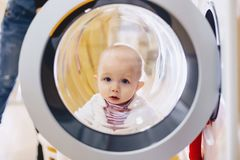 The baby looks through the window of the washing machine royalty free stock photo