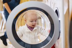 The baby looks through the window of the washing machine stock photos