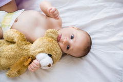 Baby lying on baby bed Stock Images