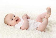 Baby lying on back smiling. Portrait of a cute young baby lying on back over a white blanket, wearing a bodysuit shirt Royalty Free Stock Images