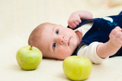 Baby lying on the bed with apples Royalty Free Stock Image