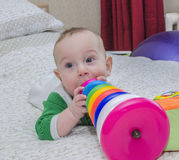 Baby lying on the bed biting a toy. Royalty Free Stock Photos