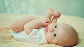 Baby Lying in Bed at Home Eating its Feet. Baby`s lying on a soft linen in bed at home, eating its feet. Soft focus, Close-up shot Stock Photo
