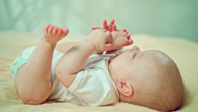 Baby Lying in Bed at Home Eating its Feet. Baby`s lying on a soft linen in bed at home, eating its feet. Soft focus, Close-up shot Royalty Free Stock Images