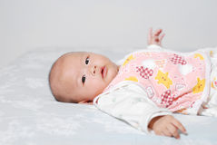 Baby lying in bed Royalty Free Stock Images