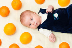 Baby lying on the bed with oranges Stock Images